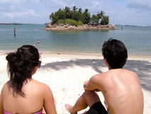 Couple at tropical seaside. Resort living with suntanning. A lady and boyfriend wearing sunglasses. Location is Sentosa in Singapore Stock Photo