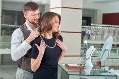 Couple trying, choising pearl necklace at jewelry store. Couple of brunette women with wavy hair wearing black dress and handsome man, trying necklace at royalty free stock photography