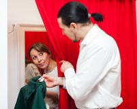 Couple trying coat in fitting-room Royalty Free Stock Photography