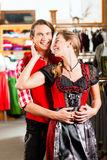 Couple is trying Dirndl or Lederhosen in a shop Royalty Free Stock Photography