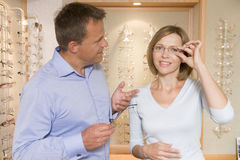 Couple trying on eyeglasses at optometrists. Smiling Royalty Free Stock Photo