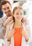 Couple trying golden pendant on at jewelry store Royalty Free Stock Photography