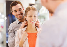 Couple trying golden pendant on at jewelry store Stock Photo
