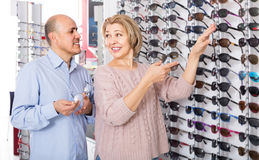 Couple trying spectacles frames and smiling near stand Stock Photos