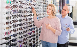 Couple trying spectacles frames and smiling near stand Stock Images