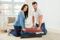 Couple trying to close suitcase with to much clothes Stock Photos