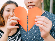 Couple trying to connect two pieces of paper heart - relationshi Stock Photography
