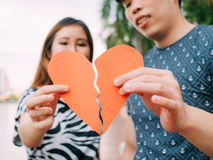 Couple trying to connect two pieces of paper heart - relationshi Royalty Free Stock Image