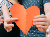 Couple trying to connect two pieces of paper heart - relationshi Stock Photo