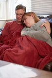 Couple Trying To Keep Warm Under Blanket At Home Stock Photo