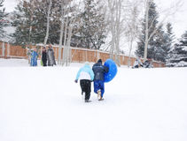 Couple Tubing. Young couple tubing at a park in fresh falling snow Royalty Free Stock Image