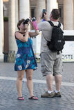 Couple turist taking a souvenir snapshot. A couple of tourists at the Vatican City take a picture / woman with a compact camera and the man with a smartphone Stock Photo