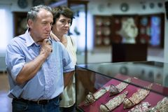 Couple turists examines the exhibit in historical museum. Mature couple turists examines the exhibit in historical museum Royalty Free Stock Images