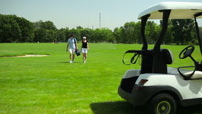 The couple turn back to the cart at the course stock footage