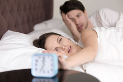 Couple turning off or snoozing alarm clock, waking up problem Royalty Free Stock Photos