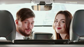 Couple turns their faces to the back seat inside the car. Attractive caucasian couple turning their faces to the back seat inside the car. Handsome man and stock video footage
