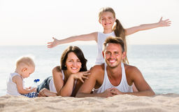 Couple with two children lying on beach Royalty Free Stock Images