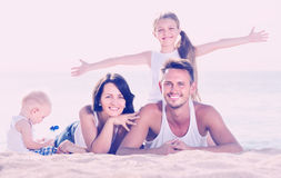 Couple with two children lying on beach Royalty Free Stock Photos