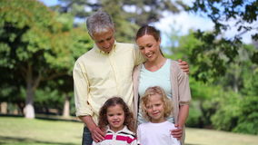 Couple with two children posing. In a park stock footage