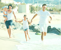 Couple with two children running Stock Photos
