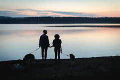 Couple with two dogs on beach. Back view of two silhouettes with dogs holding hands on coastline Stock Images