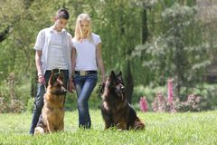 Couple with two dogs on natural background Royalty Free Stock Image