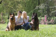 Couple with two dogs on natural background Royalty Free Stock Images