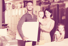 Couple with two kids holding box with electronics Stock Photo