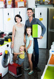 Couple with two kids holding box with new electronics Royalty Free Stock Image