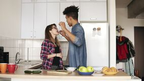 A couple of two playful young people, with urban modern hipster stylish outfits, enjoying their time together, dancing. In the kitchen. Living together goals stock video