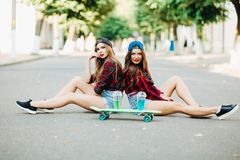 Two hipster girls sitting on ground and posing with skateboard. royalty free stock images