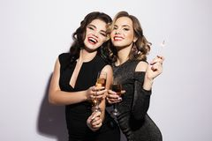 Couple of two rich women laughing with crystal of champagne. Luxury. Party time. Couple of two young rich women laughing with crystal of champagne. Luxury royalty free stock image