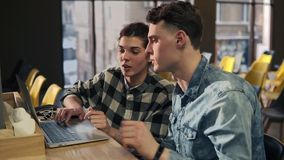 Couple of two young attractive people sitting in front of laptop talking about, discussing something. Couple of two young attractive people sitting in front of stock video footage