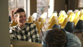 Couple of two young people are laughing together while discussing something. Indoors footage. Love, romantic feelings. Youth stock video footage