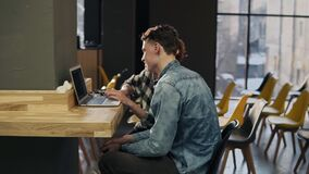 Couple of two young people sitting in an empty indoors area of co-working space, looking at photos on laptop screen. Couple of two young people sitting in an stock footage