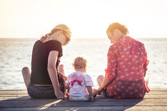 Couple of two young women with child sitting on wooden pier during sunset with horizon over sea during vacation. Stock Photography