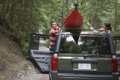 Couple Tying Kayak On Car Roof  Stock Photo