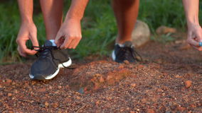 Couple tying their laces of running shoes. In forest stock video footage