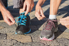 Couple tying their laces of running shoes Royalty Free Stock Photo