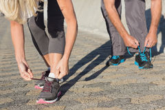 Couple tying their laces of running shoes Royalty Free Stock Image
