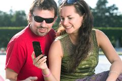 Couple typing text message. A couple looking into the mobile phone/taking photo of themselves with a mobile phone/typing text message Royalty Free Stock Images