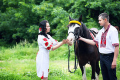 Couple in Ukrainian costumes with a horse Royalty Free Stock Photography