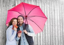 Couple with umbrella against wooden background Royalty Free Stock Images