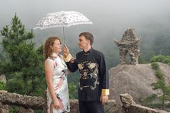 Couple with umbrella at cloudy weather on top of the Chinese mountain of Huangshan Stock Photos