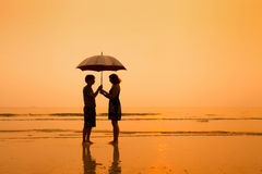 Couple with umbrella. Family on the beach, silhouettes of couple with umbrella Stock Image