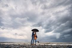 Couple with umbrella near stormy sea Stock Photo