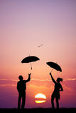 Couple with umbrella at sunset Royalty Free Stock Photo