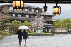 Couple with umbrella walk out from Arashiyama railway station Royalty Free Stock Photo