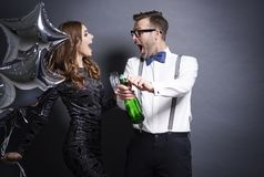 Couple celebrating New Year`s Eve. Couple uncorking bottle of champagne Royalty Free Stock Photo