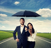 Couple under black umbrella at outdoor Stock Photos